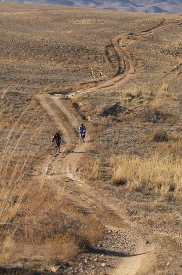 Fietsers in land (woestijn) weg stock afbeeldingen