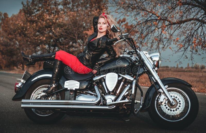 Fietservrouw met motorfiets op de weg stock foto's