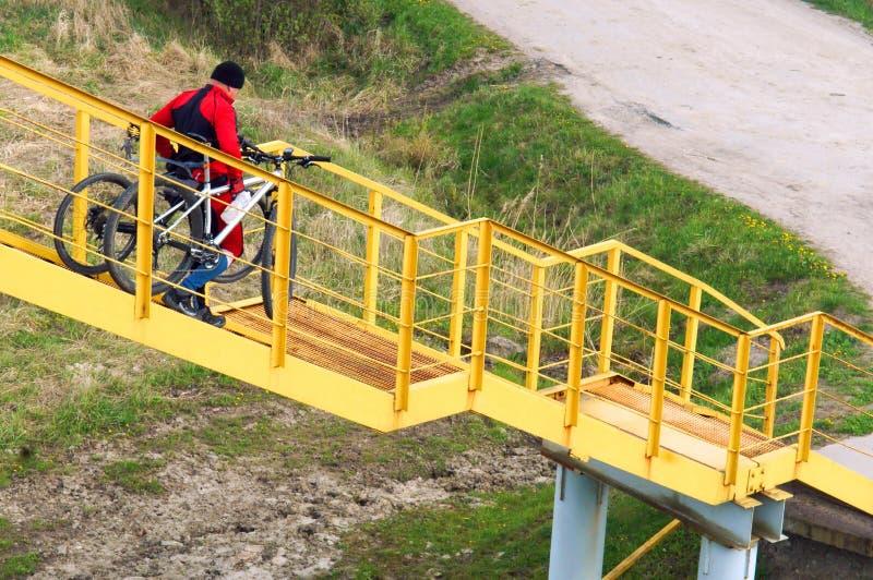 Fietslift, een ladder, die draagt, handen, sterke mens, de opheffen stock afbeelding