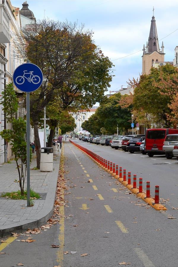 Fietspad tussen de stoep en de rijweg op een smalle straat in het oude deel van de stad Gezonde Levensstijl Cityscape  stock fotografie
