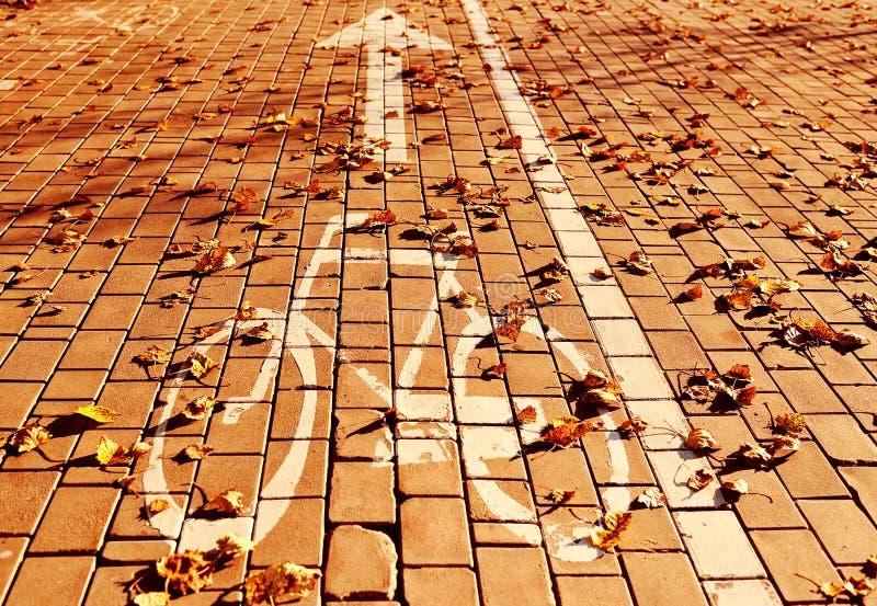 Fietsteken op de weg op de achtergrond van gele bladeren royalty-vrije stock foto's