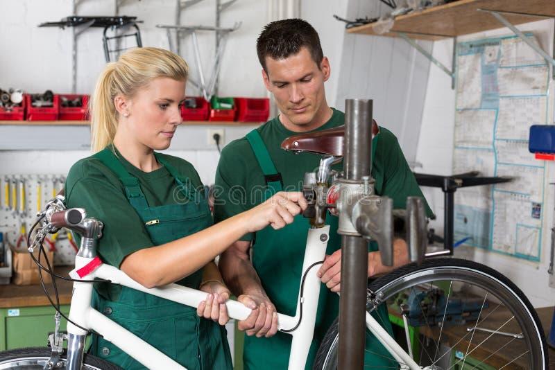 Fietswerktuigkundige en leerling die een fiets herstellen stock afbeeldingen