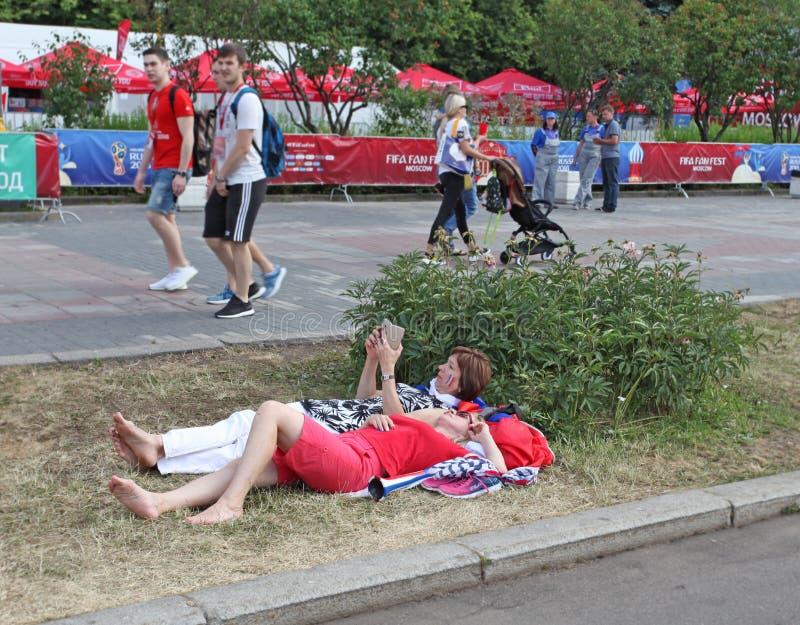 FIFA 2018 fans som kopplar av på gräset i kullar för fanzonsparv, Moskva, Ryssland arkivfoto