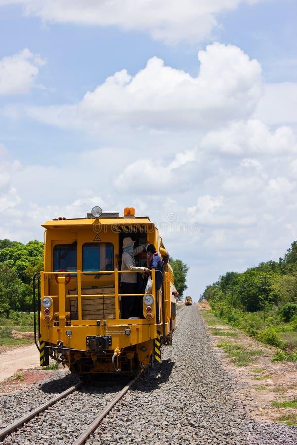 Fiffla barlast, tampingmaskin bygger den nya järnvägen. royaltyfri foto