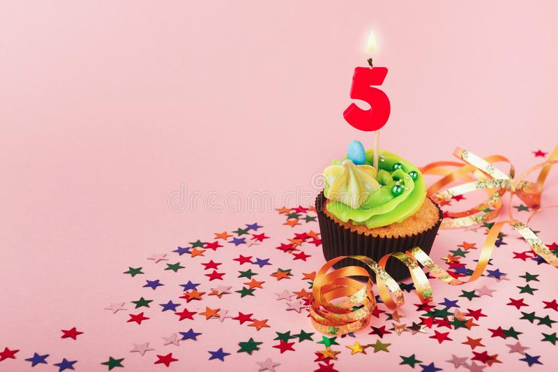 Fifth birthday cupcake with candle and sprinkles. Fifth 5th birthday cupcake with candle and sprinkles on pink background. Card mockup, copy space. Birthday royalty free stock images
