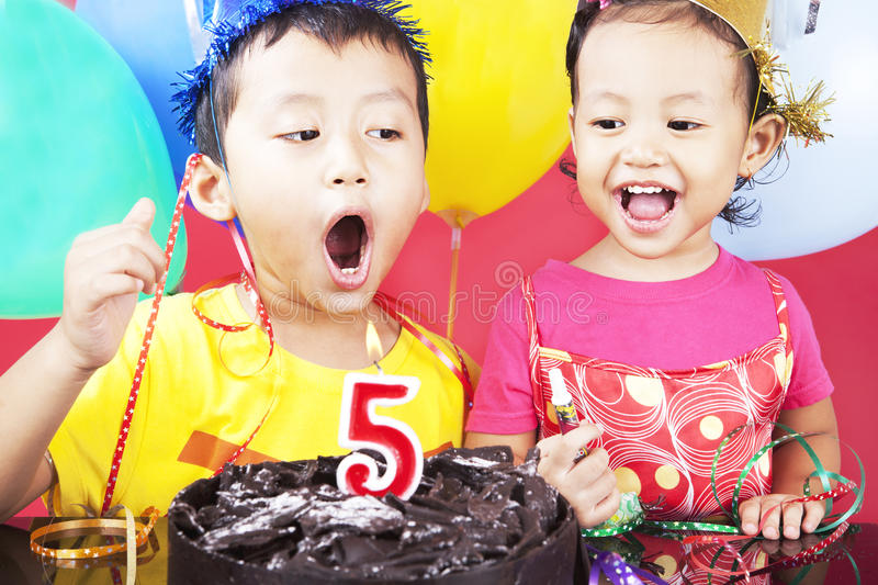 Fifth birthday party. Asian sibling celebrating fifth birthday, shot in studio at birthday party stock image