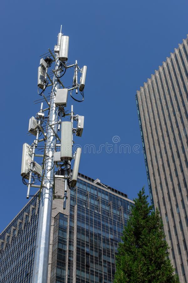 Fifth generation cell tower. Cellular communications against the background of an office building and blue sky. GSM 5G royalty free stock images