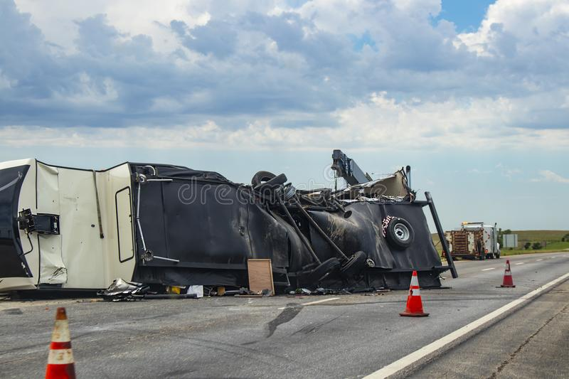 Fifth wheel Recreational Vehicle overturned on a highway with the underside torn up and things spilling out into the roadway after stock photo