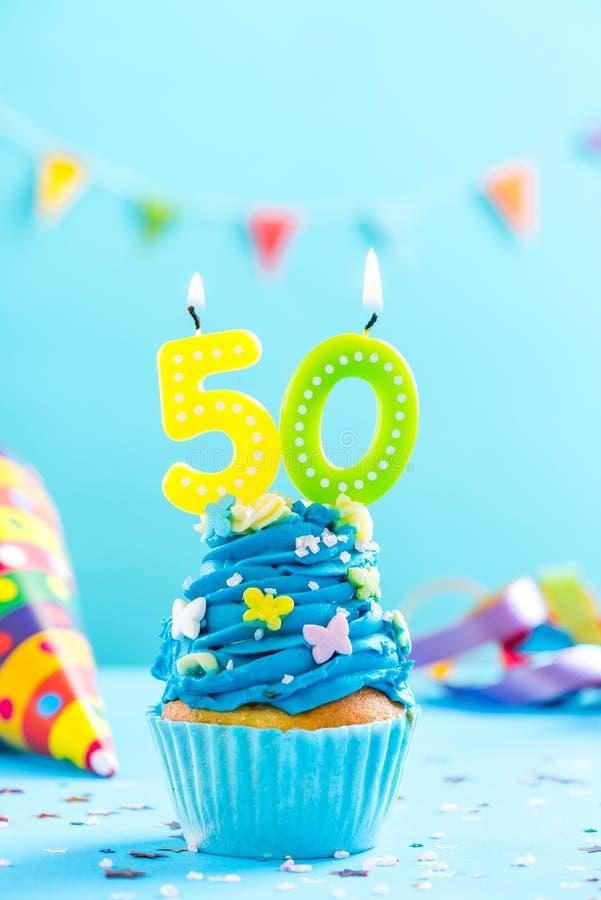 Fiftieth 50th urodzinowa babeczka z świeczką Karciany mockup obraz royalty free