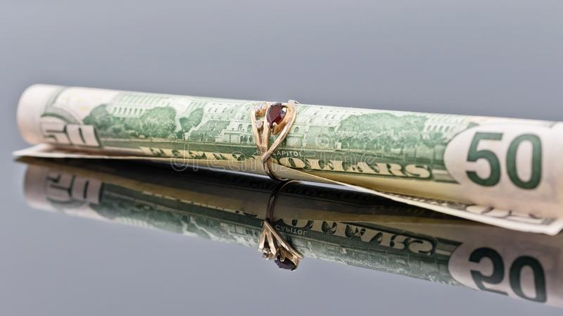 Fifty dollar bill is rolled into elegant women`s gold ring stock images