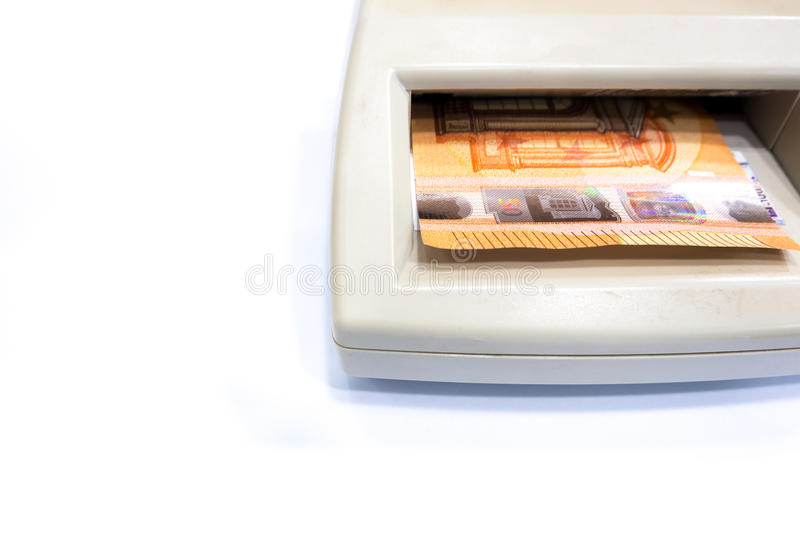 Fifty euro banknote in automatic counterfeit money detector on w. Counterfeit money detection, fifty euro banknote in automatic counterfeit money detector on royalty free stock image