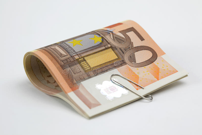 Fifty Euro bills clipped. Fifty Euro bills with paperclip on white background stock photo