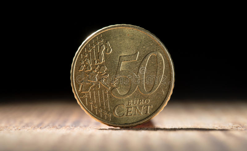 Fifty euro cents close up on wooden table. On black background royalty free stock photography