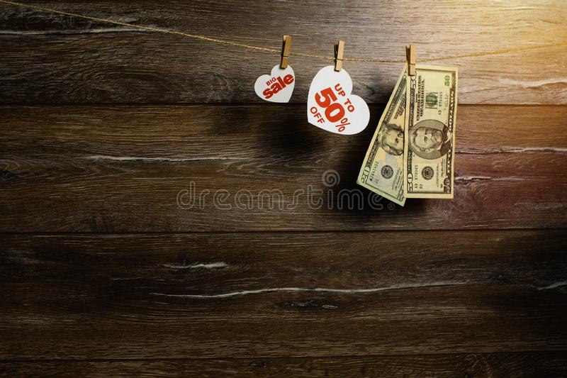 Fifty percent at big sale for holiday of love in heart near american money drying on a rope by clothespins. stock photography
