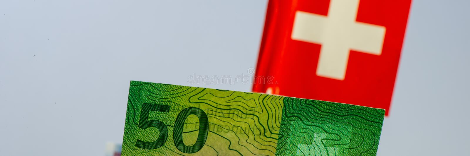 Fifty Swiss francs bill on flag background stock photo