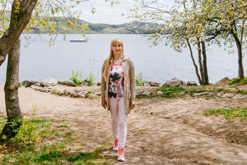 Fifty-year-old blonde woman in a cardigan stands on the shore of the Lake stock images