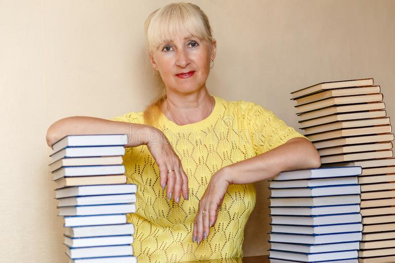Fifty-year-old woman in a yellow sweater sitting at a table with books. Indoors stock photos