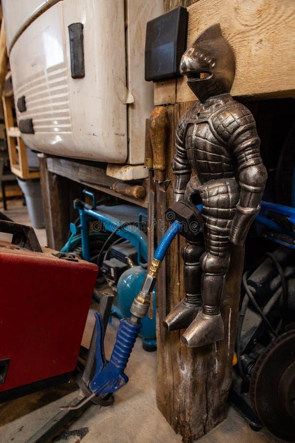 Figürchen, die einen Luftkompressorschlauch hält lizenzfreies stockfoto