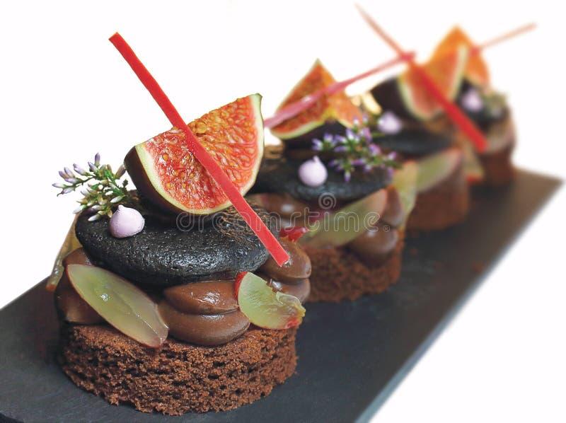 Fig. en de zwarte taartjes van het macarondessert met druiven, schuimgebakjes, de lente bloeien en rode chocoladedecoratie royalty-vrije stock afbeeldingen
