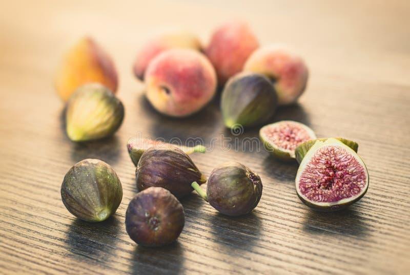 Fig. en perziken op een lijst stock afbeeldingen