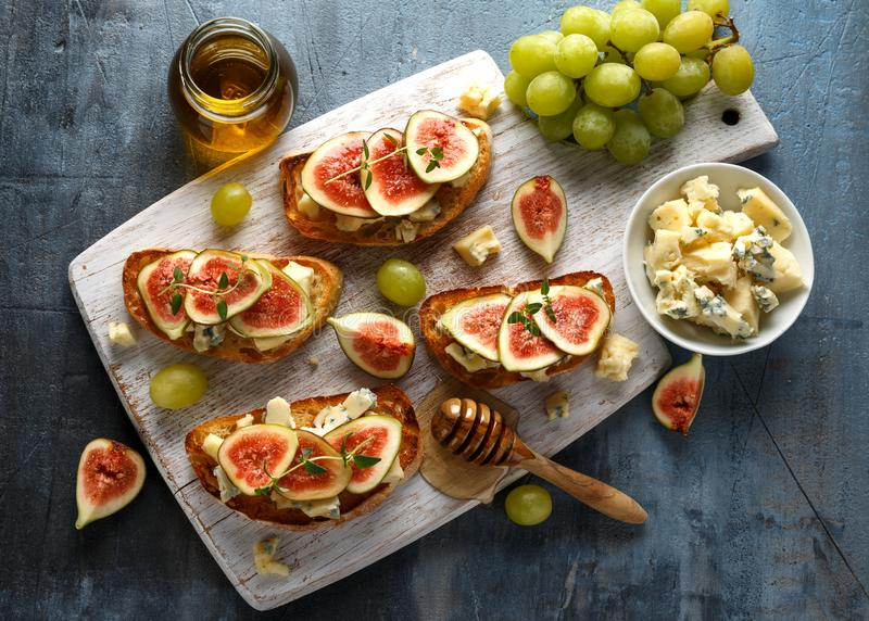 This Fig and Gorgonzola tartines, toast, bruschetta. drizzled with honey on white wooden board stock image