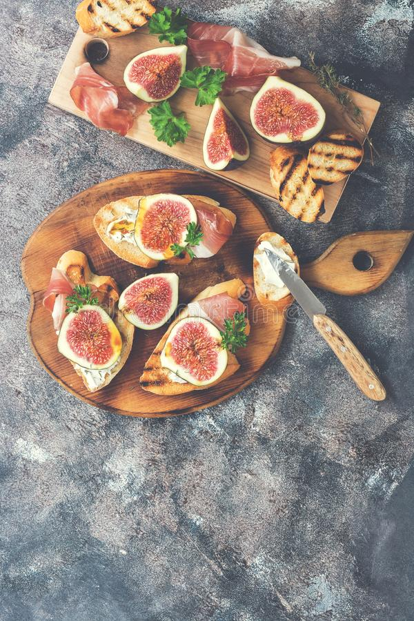 Fig with ham, cheese and toast. Prosciutto with figs on a rustic background. Top view, overhead, flat lay.Space for text. royalty free stock photo