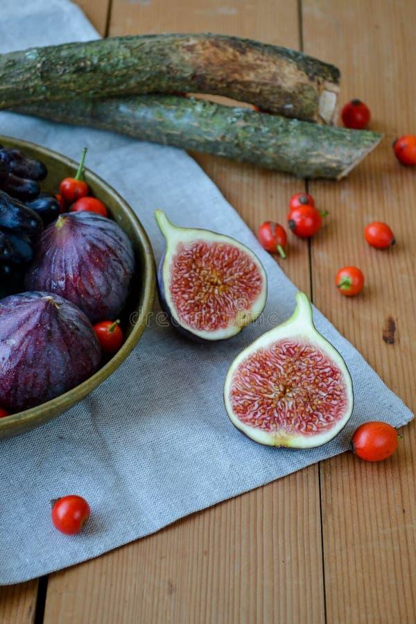 Fig. op een houten achtergrond met rozebottel en druiven stock fotografie