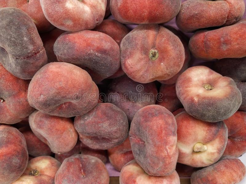 Fig peach. saturn peaches. flat peaches harvest. many peaches. Fresh fruit at farmers` market: peaches. fig peach background. Close-up stock photo