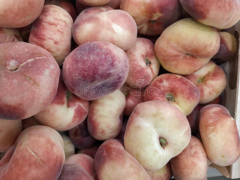 Fig peach. saturn peaches. flat peaches harvest. many peaches. Fresh fruit at farmers` market: peaches. fig peach background. Close-up royalty free stock image