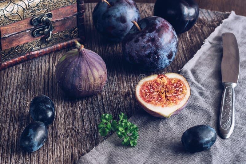 Fig. wordt gesneden op een houten lijst met druiven en pruimen Stilleven met fig Selectieve nadruk stock afbeeldingen