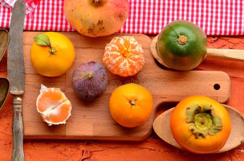 Figa, persimmon, granatowiec, avocado i mandarynki na szorstkim tle, (tangerines) Wciąż życie temat zdjęcie royalty free