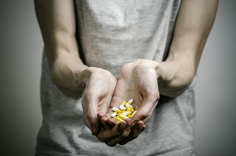 The fight against drugs and drug addiction topic: addict holding a narcotic pills on a dark background royalty free stock images