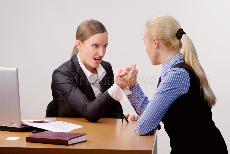 Fight of businesswomen. Two young businesswomen arm wrestling at the desk in office royalty free stock photo