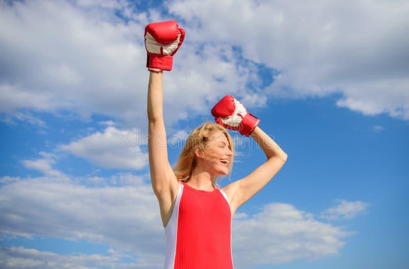 Fight for female rights. Girl leader promoting feminism. Woman boxing gloves raise hands blue sky background. Girl. Boxing gloves symbol struggle for female stock image