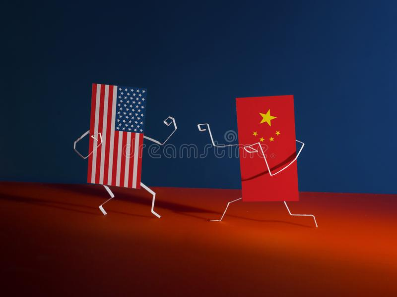 Fight between paper flags of the USA and China. Figures cut out of paper. Allegory of Economic War royalty free stock image