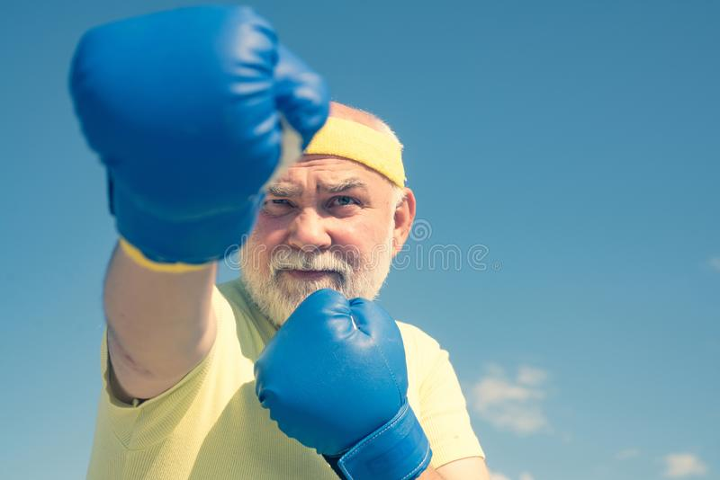 Fighter. Boxer with boxing glove. Senior man in gloves beats punching bag. Boxing. Older man boxing. I love boxing stock photography