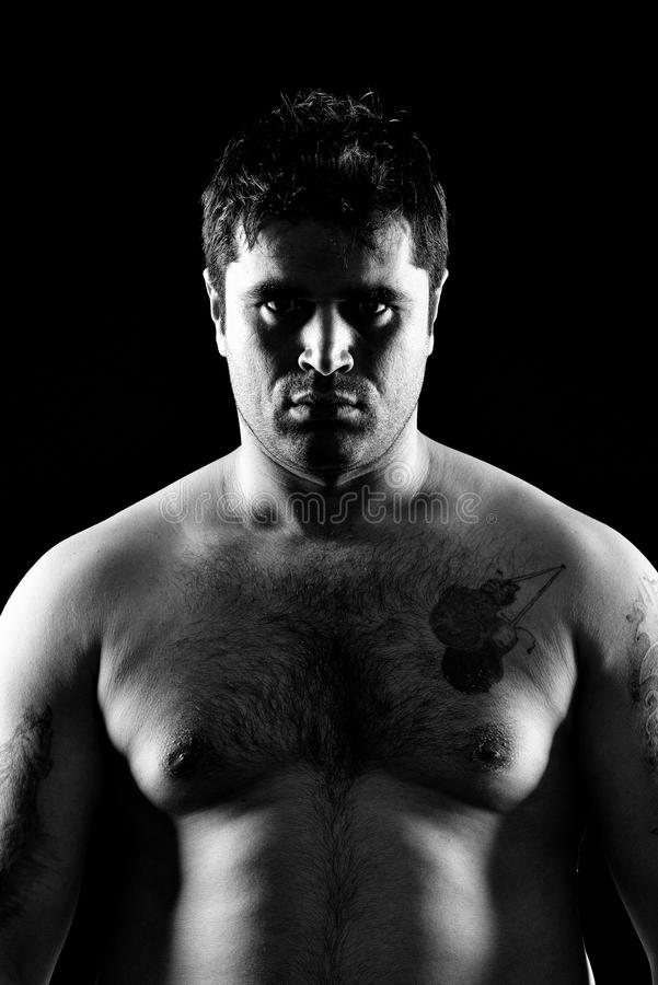 Fighter boxer portrait. Fighter boxer standing staring strong on black background. Young masculine caucasian male athlete in his 20s. Black and white photo royalty free stock image