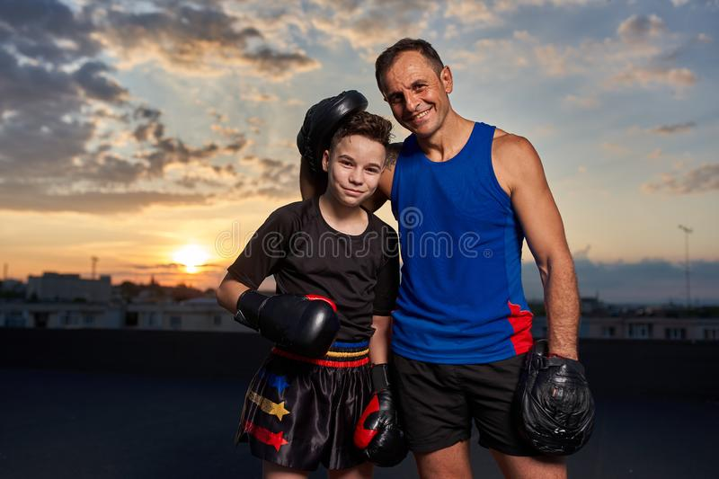 Fighter and coach posing. Young fighter and coach posing after training at sunset royalty free stock images
