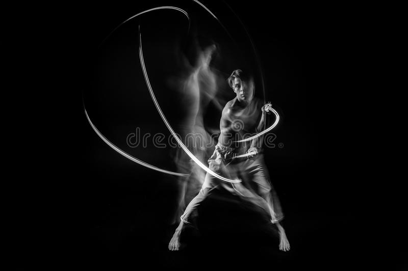 Fighter in the dark with lightsaber. long exposure. Emotional male portrait. royalty free stock photo