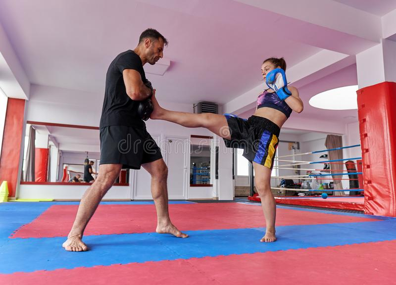 FIghter girl and coach. Young girl muay thai fighter and her coach hitting mitts in the ring royalty free stock photo