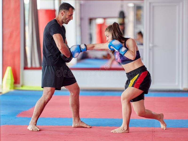 FIghter girl and coach. Young girl muay thai fighter and her coach hitting mitts in the ring stock images