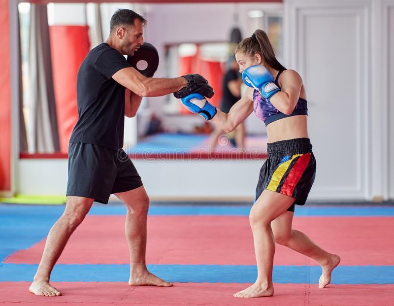 FIghter girl and coach. Young girl muay thai fighter and her coach hitting mitts in the ring stock photography