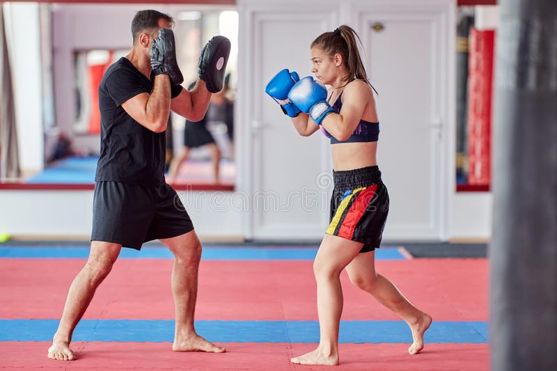 FIghter girl and coach. Young girl muay thai fighter and her coach hitting mitts in the ring stock photos