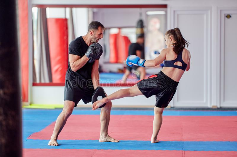 FIghter girl and coach. Young girl muay thai fighter and her coach hitting mitts in the ring royalty free stock photos