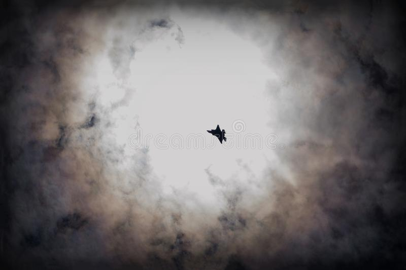 A fighter jet silhouette in dramatic skies royalty free stock images