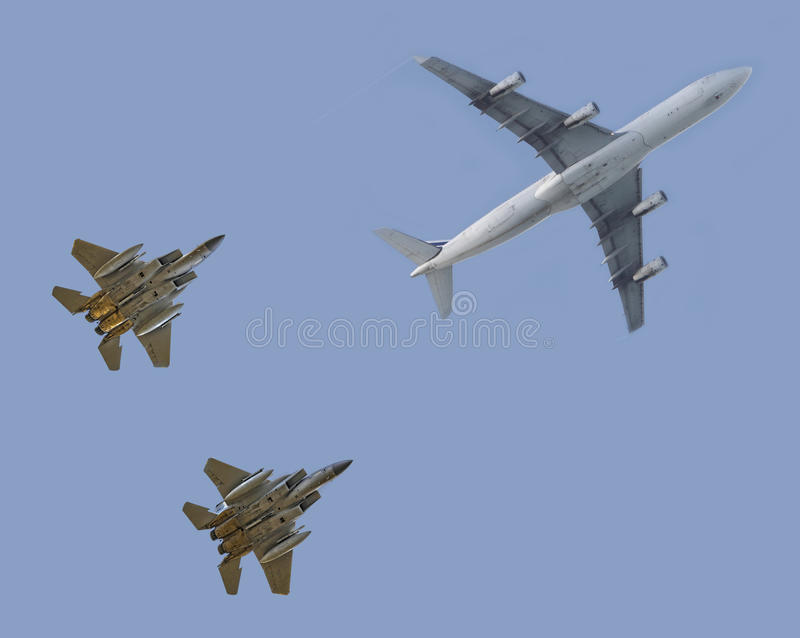 Fighter jets escorting passenger airplane royalty free stock photography