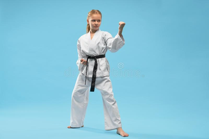 Fighter in kimono looking aside and fighting in studio. Angry female fighter in kimono looking aside and fighting in studio. Concentrated sporty child doing royalty free stock images