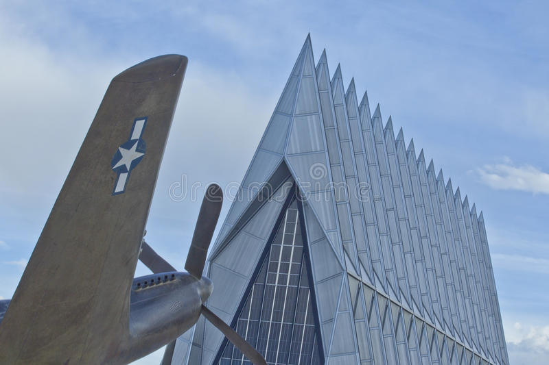 Fighter Plane at Air Force Academy Chapel, CO. World War II-era fighter plane stands as a sentinel in front of the cadet chapel at the United States Air Force royalty free stock image