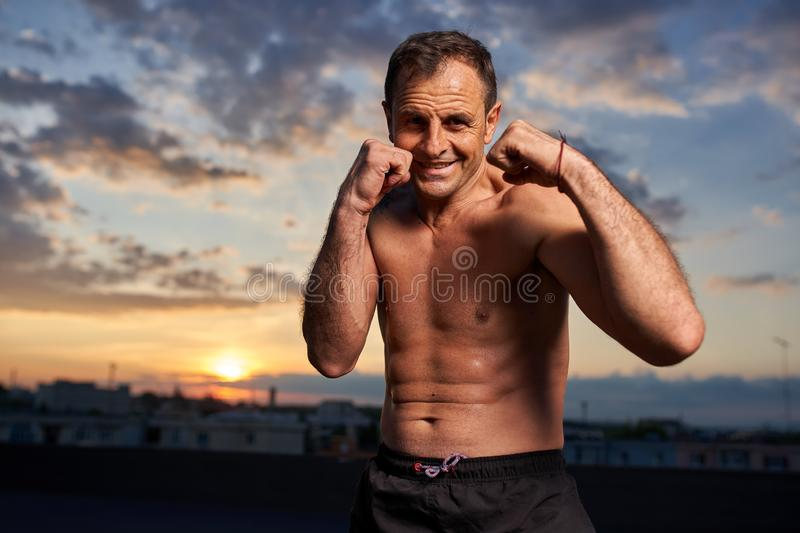 Fighter posing at sunset. In guard stance royalty free stock photography