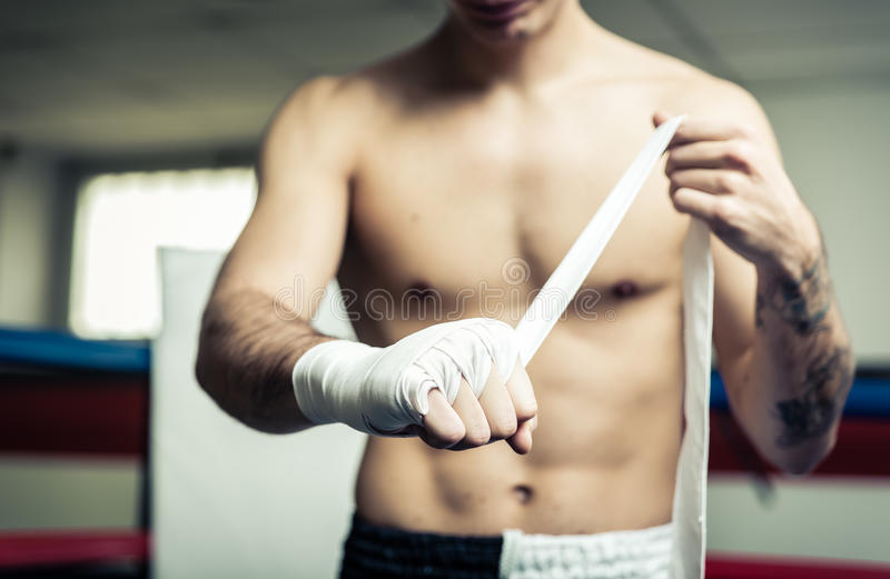 Fighter putting bendage on the hands stock photography